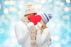 Smiling couple in winter clothes with red heart. Love, valentines day, couple, christmas and people concept - smiling men and women in winter hats and scarf Stock Photo