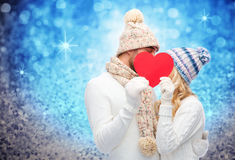 Smiling couple in winter clothes with red heart. Love, valentines day, couple, christmas and people concept - smiling men and women in winter hats and scarf Royalty Free Stock Photography