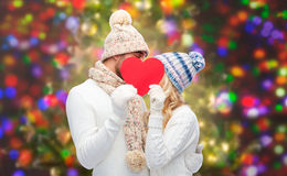 Smiling couple in winter clothes with red heart. Love, valentines day, couple, christmas and people concept - smiling men and women in winter hats and scarf Royalty Free Stock Image