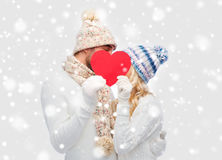 Smiling couple in winter clothes with red heart. Love, valentines day, couple, christmas and people concept - smiling men and women in winter hats and scarf Royalty Free Stock Photo