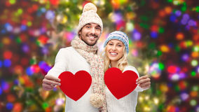 Smiling couple in winter clothes with red hearts Royalty Free Stock Images
