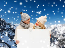 Smiling couple in winter clothes with white board. Winter, holidays, christmas, advertisement and people concept - smiling couple in winter clothes with white Royalty Free Stock Photo