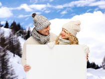 Smiling couple in winter clothes with white board Stock Photography