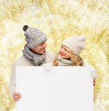 Smiling couple in winter clothes with white board Stock Photo