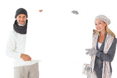 Smiling couple in winter fashion holding poster Royalty Free Stock Images