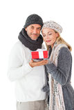 Smiling couple in winter fashion holding present Royalty Free Stock Photography