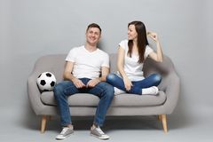 Smiling couple woman man football fans cheer up support favorite team holding bitcoin, future currency isolated on grey. Smiling couple women men football fans royalty free stock image