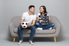 Smiling couple woman man football fans cheer up support favorite team with soccer ball holding classic black film making. Clapperboard isolated on grey royalty free stock image