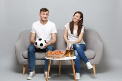 Smiling couple woman man football fans in white t-shirt cheer up support favorite team with soccer ball isolated on grey. Smiling couple women men football fans royalty free stock photos