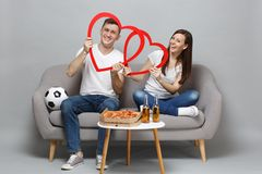 Smiling couple woman man football fans cheer up support favorite team, sitting holding big red wooden hearts isolated on. Smiling couple women men football fans royalty free stock photo