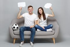 Smiling couple woman man football fans cheer up support favorite team with soccer ball, holding empty blank Say cloud. Smiling couple women men football fans stock images
