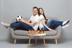 Smiling couple woman man football fans cheer up support favorite team with soccer ball, sitting back to back isolated on. Smiling couple women men football fans royalty free stock image