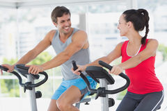 Smiling couple working out at spinning class Stock Images