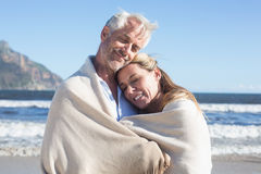 Smiling couple wrapped up in blanket on the beach Royalty Free Stock Images