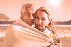 Smiling couple wrapped up in blanket on the beach Stock Photo