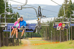 Smiling couples using chair lift scenic landscape Stock Photos