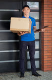 Smiling courier holding cardboard box royalty free stock photo