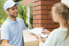 Smiling courier with a parcel. Smiling courier holding a parcel and women signing a delivery form stock photos