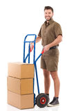 Smiling courier posing with a delivery cart Stock Image