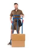 Smiling courier posing with a push cart Royalty Free Stock Images