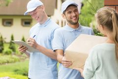 Couriers in blue uniforms and caps giving package to a customer stock images