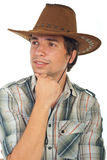 Smiling cowboy looking away. And wearing brown hat isolated on white background Royalty Free Stock Photography