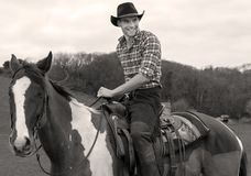 Cowboy on horseback, horse riding with chequered shirt and trees in background. A smiling cowboy sitting in the saddle on horse back riding the chequered horse stock photos