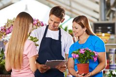 Employees in the flower shop with advice from customers. Smiling coworker in flower shop at consultation of two female customers royalty free stock photography