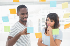 Smiling coworker reading sticky notes Royalty Free Stock Photo