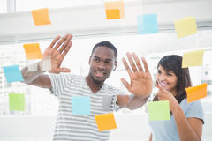 Smiling coworkers brainstorming with sticky notes Stock Photos