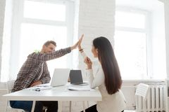 Smiling coworkers giving high five celebrating shared success royalty free stock photos