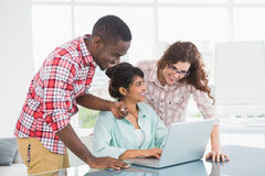Smiling coworkers interacting and using laptop. In the office Royalty Free Stock Photo