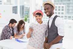 Smiling coworkers with mobile phone standing Stock Photo