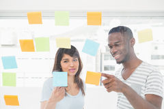 Smiling coworkers pointing sticky notes together Royalty Free Stock Images