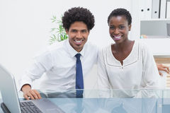 Smiling coworkers sitting and looking at camera Royalty Free Stock Images
