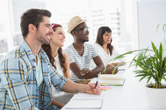 Smiling coworkers sitting and taking notes Stock Images