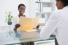 Smiling coworkers studying a document Stock Image