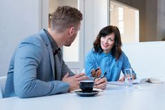 Smiling coworkers talking together in an office meeting room Royalty Free Stock Photography