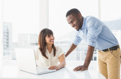 Smiling coworkers using laptop together Stock Images