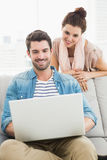 Smiling coworkers using laptop together Stock Photo