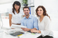 Smiling coworkers working together at desk Stock Photo