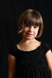 Smiling Coy Child. A dramatic closeup of a smiling dark haired, blue eyes coy little girl. Shallow depth of field stock images