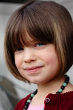 Smiling Coy Child. A closeup of a smiling dark haired, blue eyes, coy little girl. Shallow depth of field stock photos