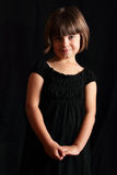 Smiling Coy Child in Black. A dramatic portrait of a smiling dark haired, blue eyes, coy little girl wearing black. Shallow depth of field royalty free stock photos