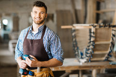 Smiling craftsman with electric drill. Waist-up portrait of smiling bearded craftsman with electric drill in hands standing in spacious workshop and looking at stock photos