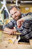 Smiling craftsman files wooden guitar neck in workshop Royalty Free Stock Photos
