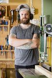 Smiling craftsman with safety mask and earmuffs in workshop Royalty Free Stock Photos