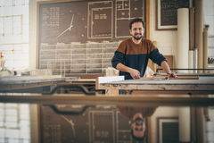 Smiling craftsman at work in his woodwork studio Stock Images