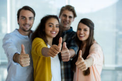 Smiling creative business team showing thumbs up in office Royalty Free Stock Photos