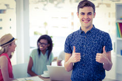 Smiling creative businessman working near co workers stock image